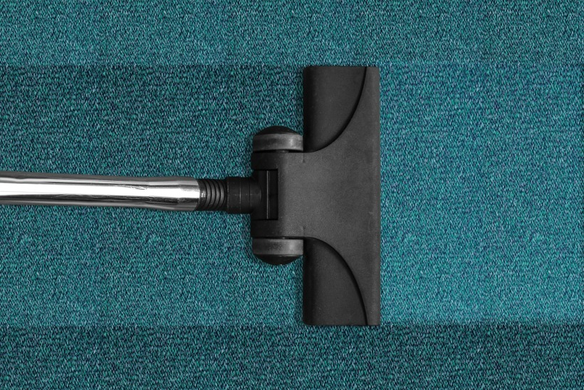 Image of a vacuum cleaner head cleaning a blue carpet