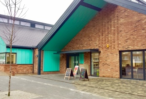 Image of the exterior of a new brick building with large windows and turquoise eaves.