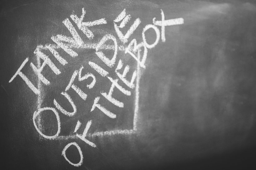 "Image of blackboard: ""think outside of the box"" is written in chalk in capital letters over a square shape."