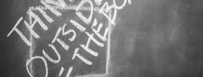 """Image of blackboard: """"think outside of the box"""" is written in chalk in capital letters over a square shape."""