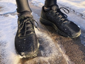 Close up of an adult's feet wearing black trainers on an icy pavement.