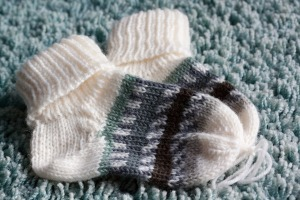 Hand knit baby socks, cream with a blue, green and brown striped section, on a blue rug.